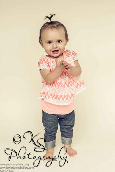 one year old girl standing and clapping